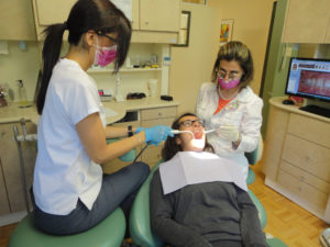 Dr Zohreh Ansari and Naz the dental assistant are working on a child's teeth