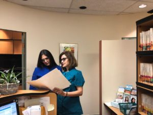 Dr Zohreh Ansari and Helen the receptionist are looking into a patient's file