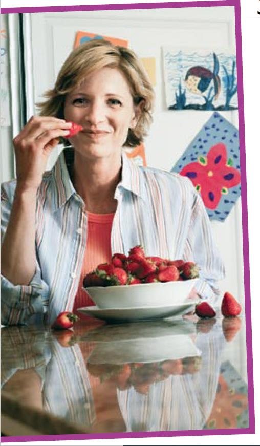 Happy lady eating strawberries